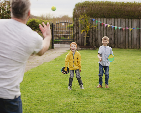 Man playing catch with his sons outside